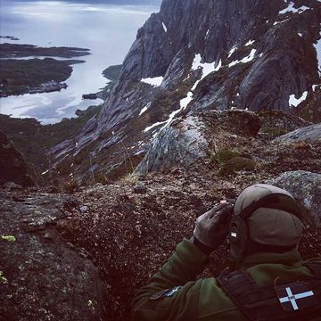 Man observing with binoculars from a hill top
